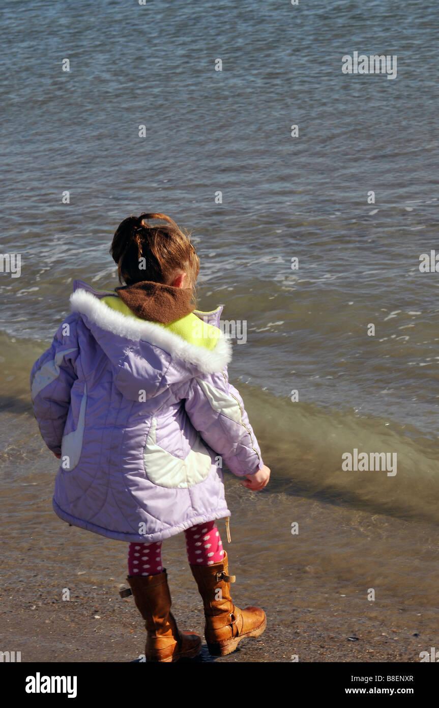 Young girl dodging waves at waters edge at seashore - Stock Image