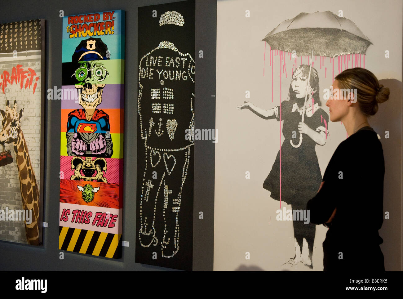 Nola Pink, showing a girl being rained upon beneath an umbrella and other Banksy works part of Bonhams auction house's - Stock Image