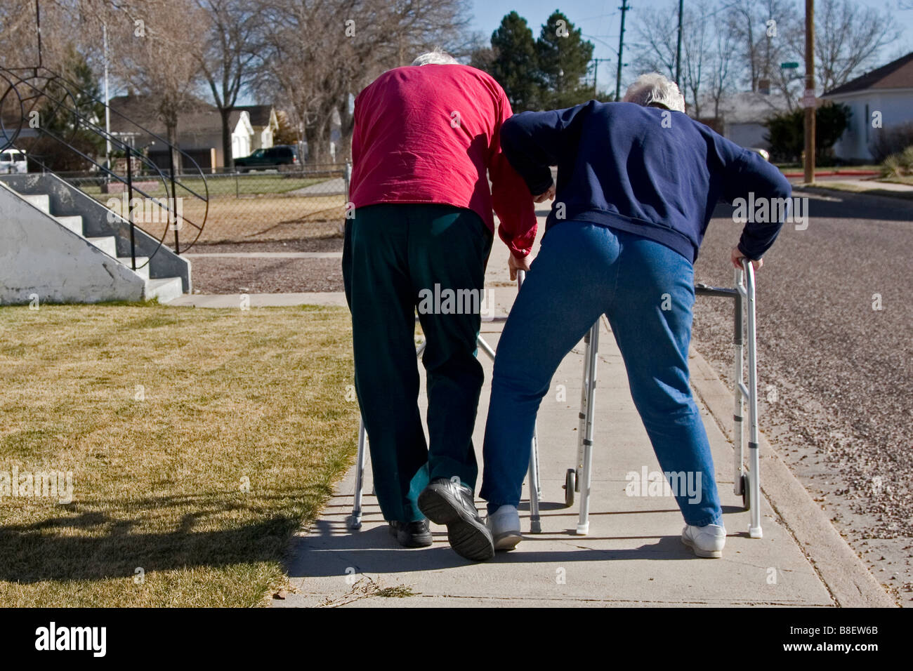 Two elderly senior citizens walk away using walkers, the woman tripping the man, humour, humor, one of four in series - Stock Image