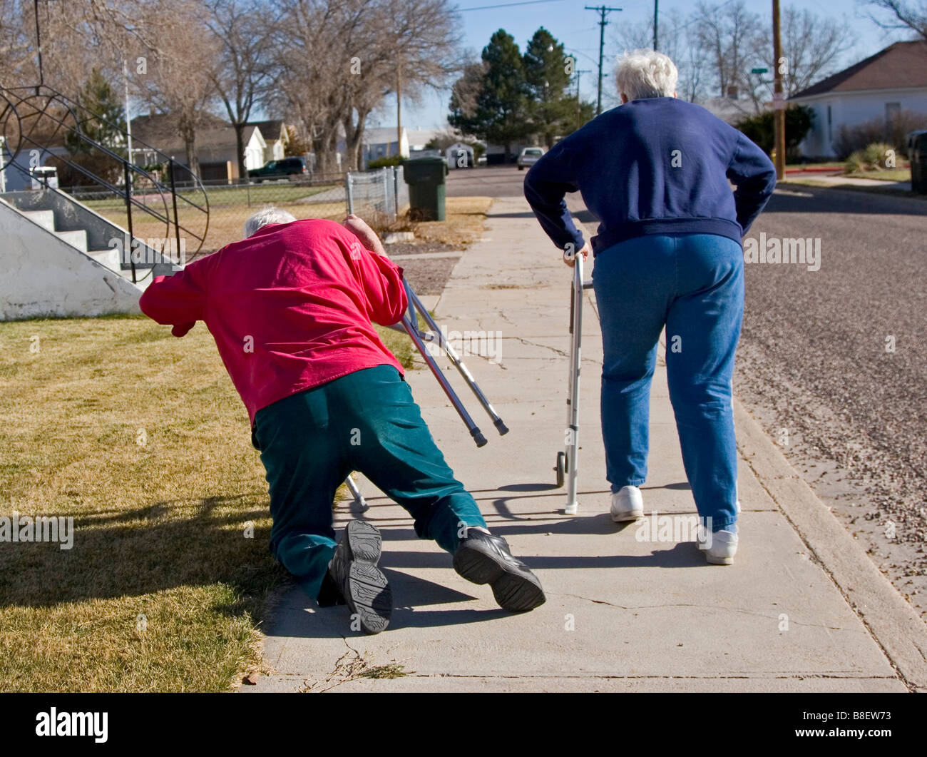 Two elderly senior citizens walk away using walkers, the woman tripped the man who is falling down, funny,  1 of Stock Photo