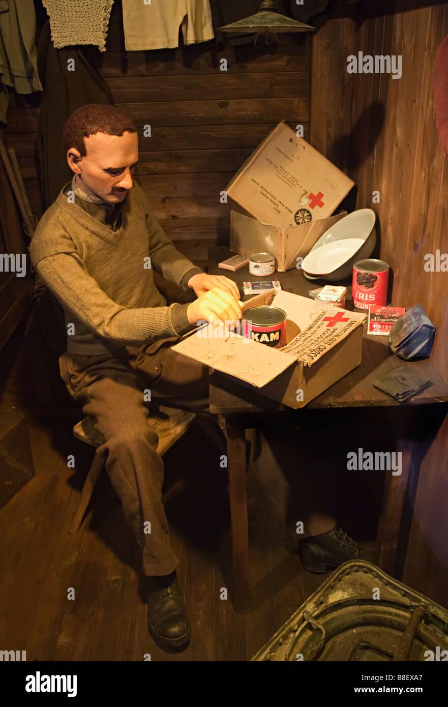 Museum model of Second World War prisoner of war soldier opening a Red Cross food parcel Arnhem Netherlands - Stock Image