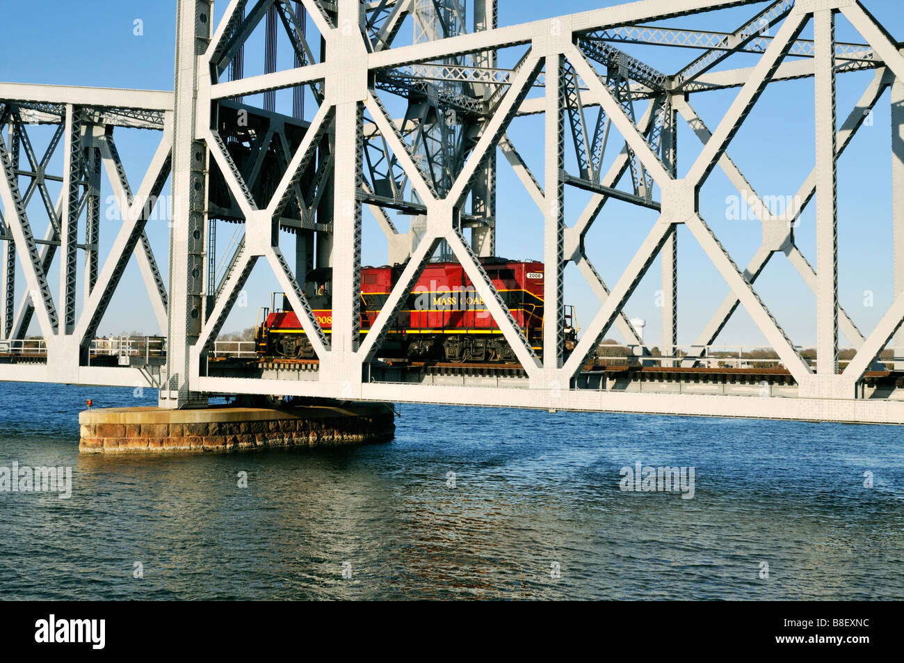 Train engine crossing the waters of the 'Cape Cod Canal' over a 'vertical lift' railroad bridge - Stock Image
