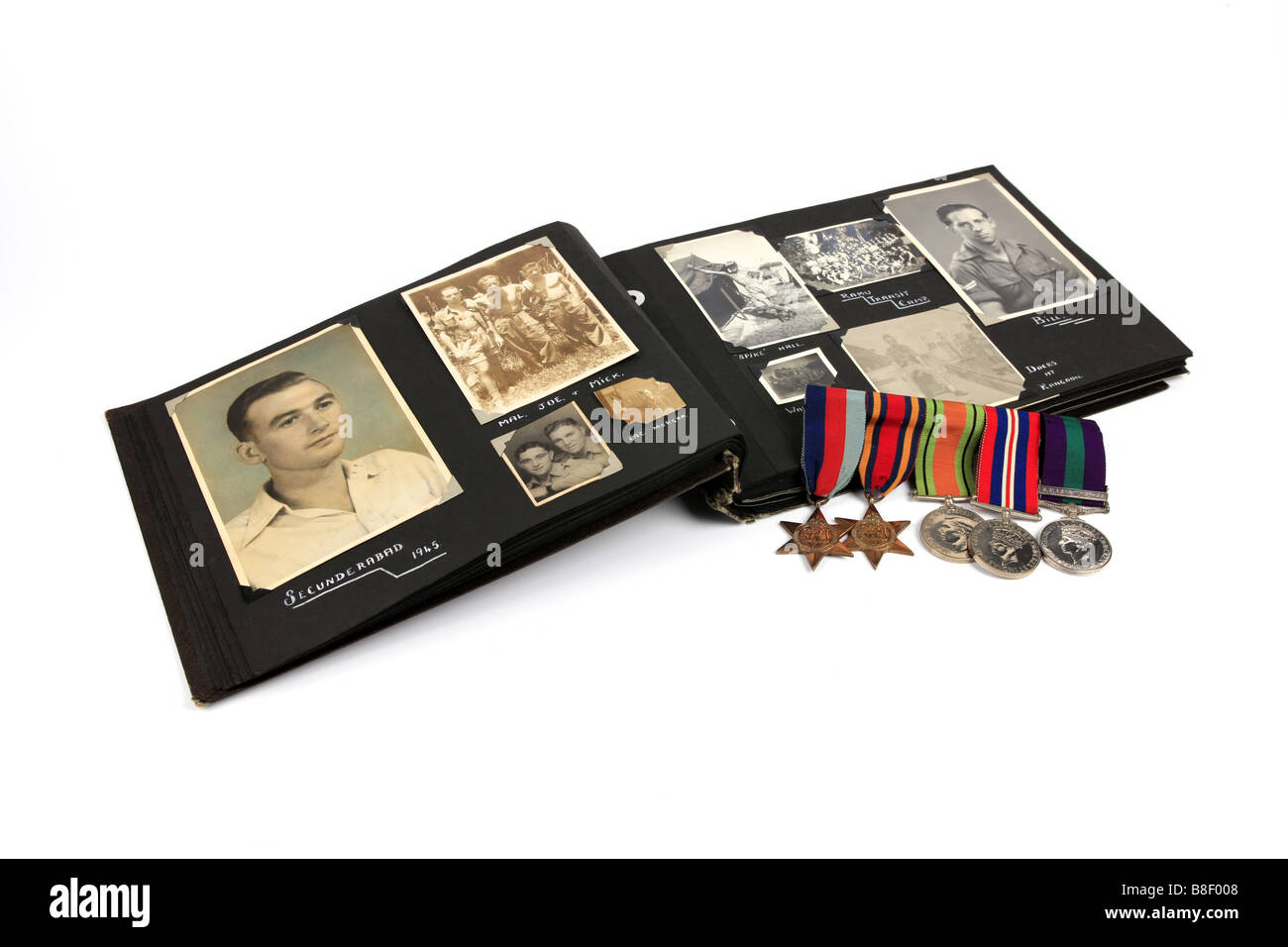 A WW2 Veteran s photo album with a group of medals against a white background - Stock Image
