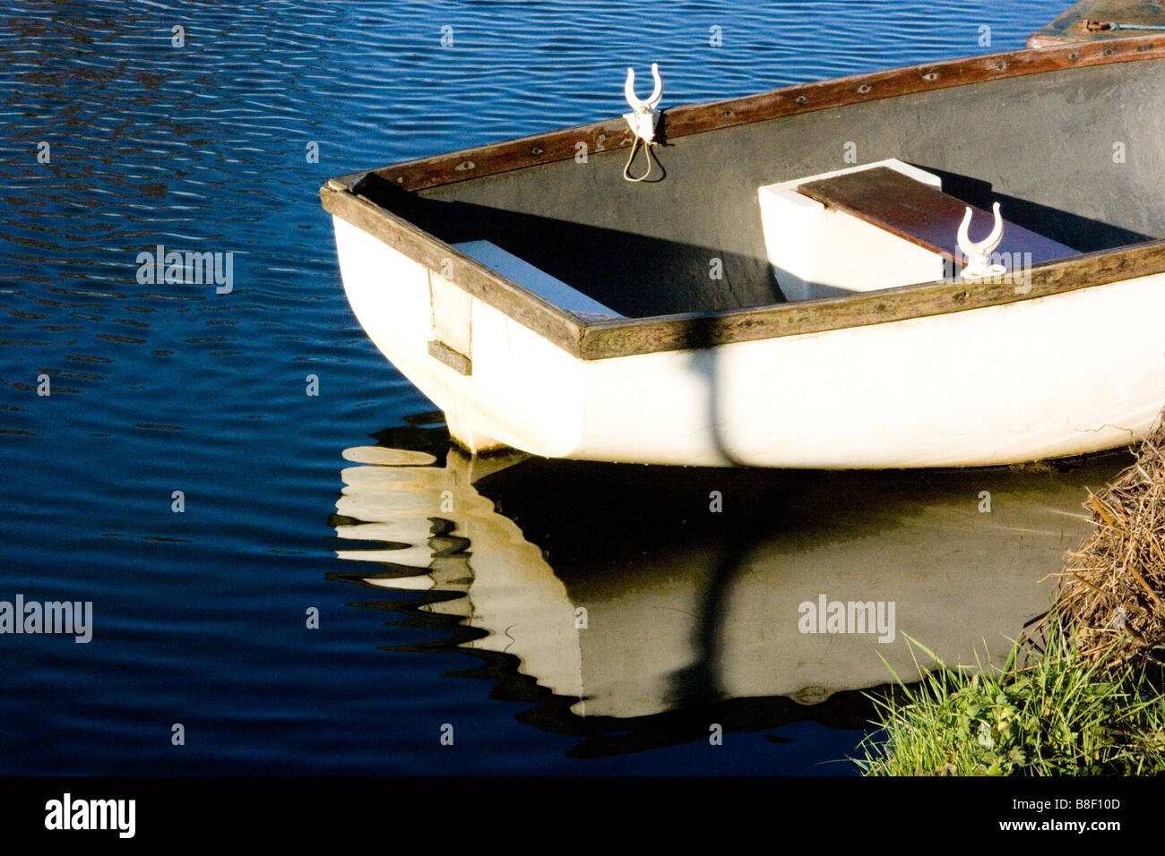 Moored white rowing boat reflected in water - Stock Image