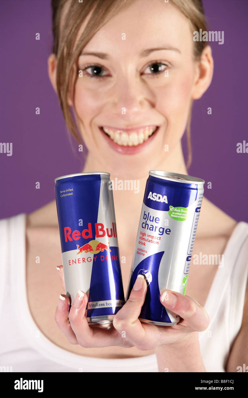 Model holding asda own brand and branded energy drinks - Stock Image