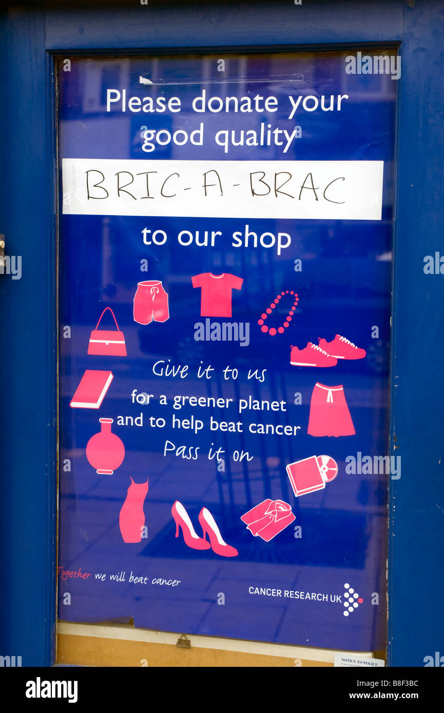 A Cancer Research Charity shop door poster asking for donations, High Street, New Malden London UK - Stock Image