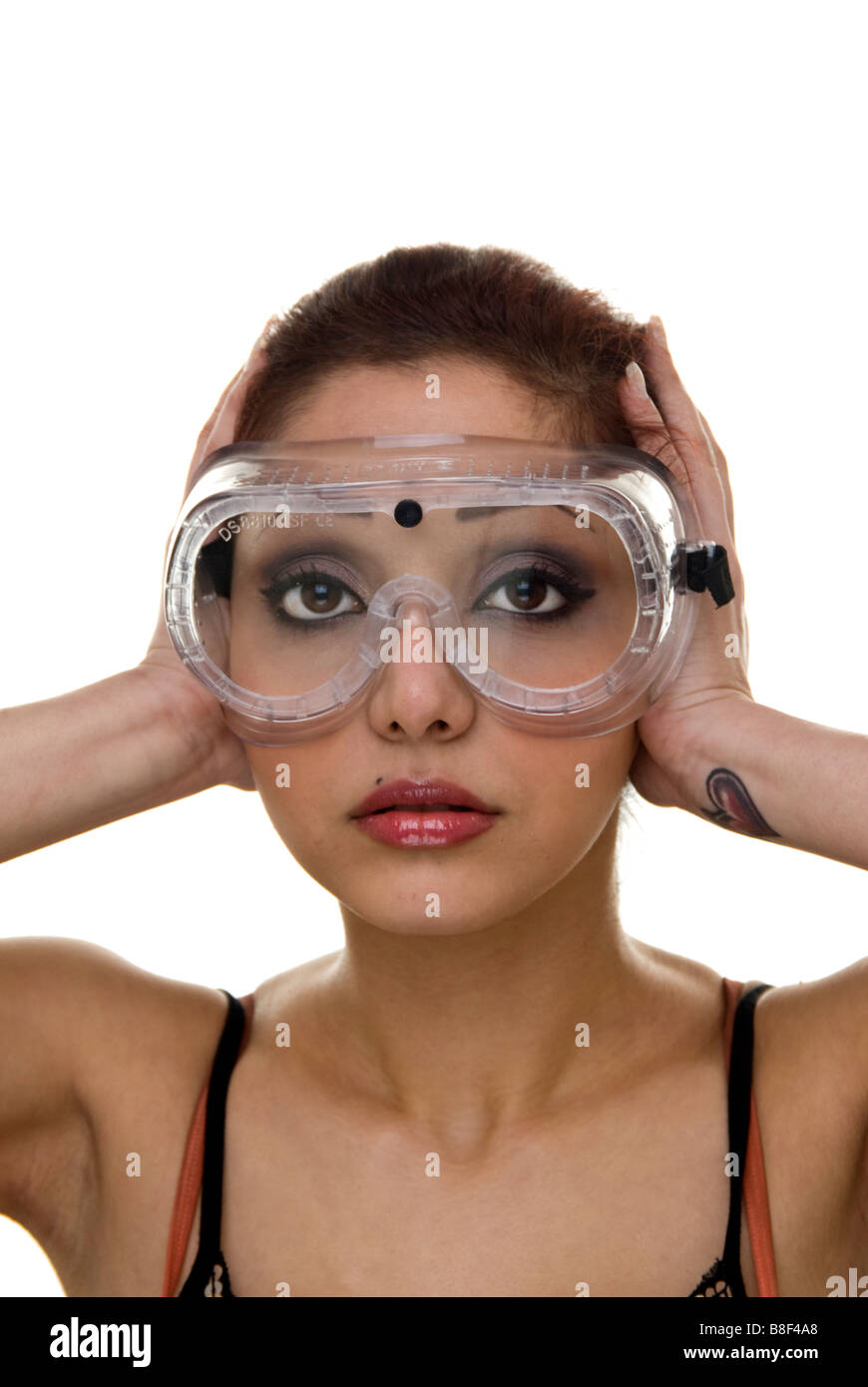 f5a1b0cba7 woman wearing safety goggles with hands over her ears Stock Photo ...