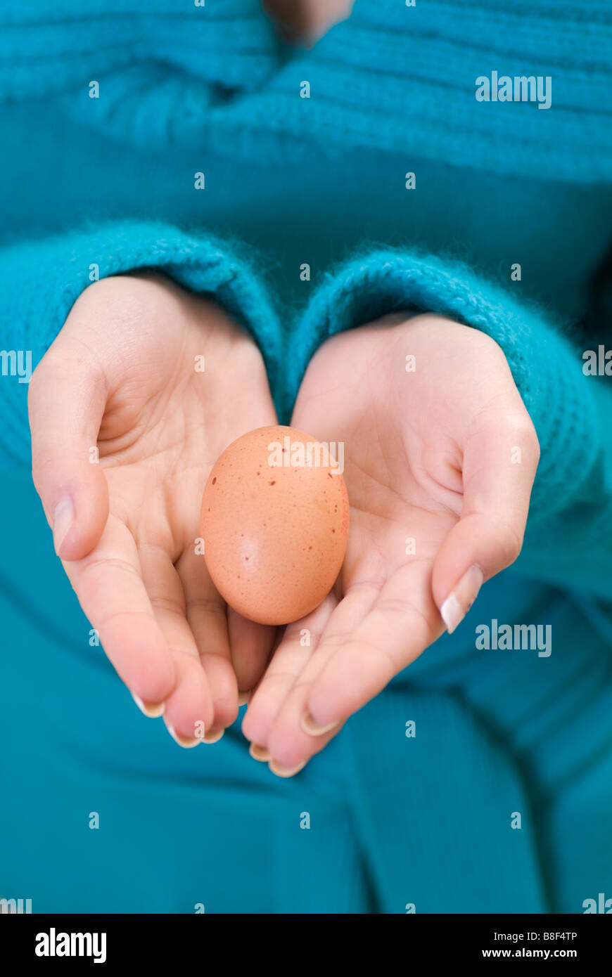 Close up of a woman's hands holding an egg - Stock Image
