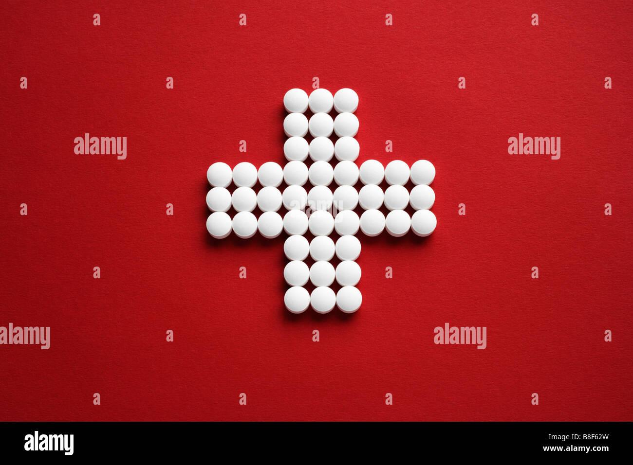 Tabletten als Kreuz gelegt auf roten Untergrund Stock Photo