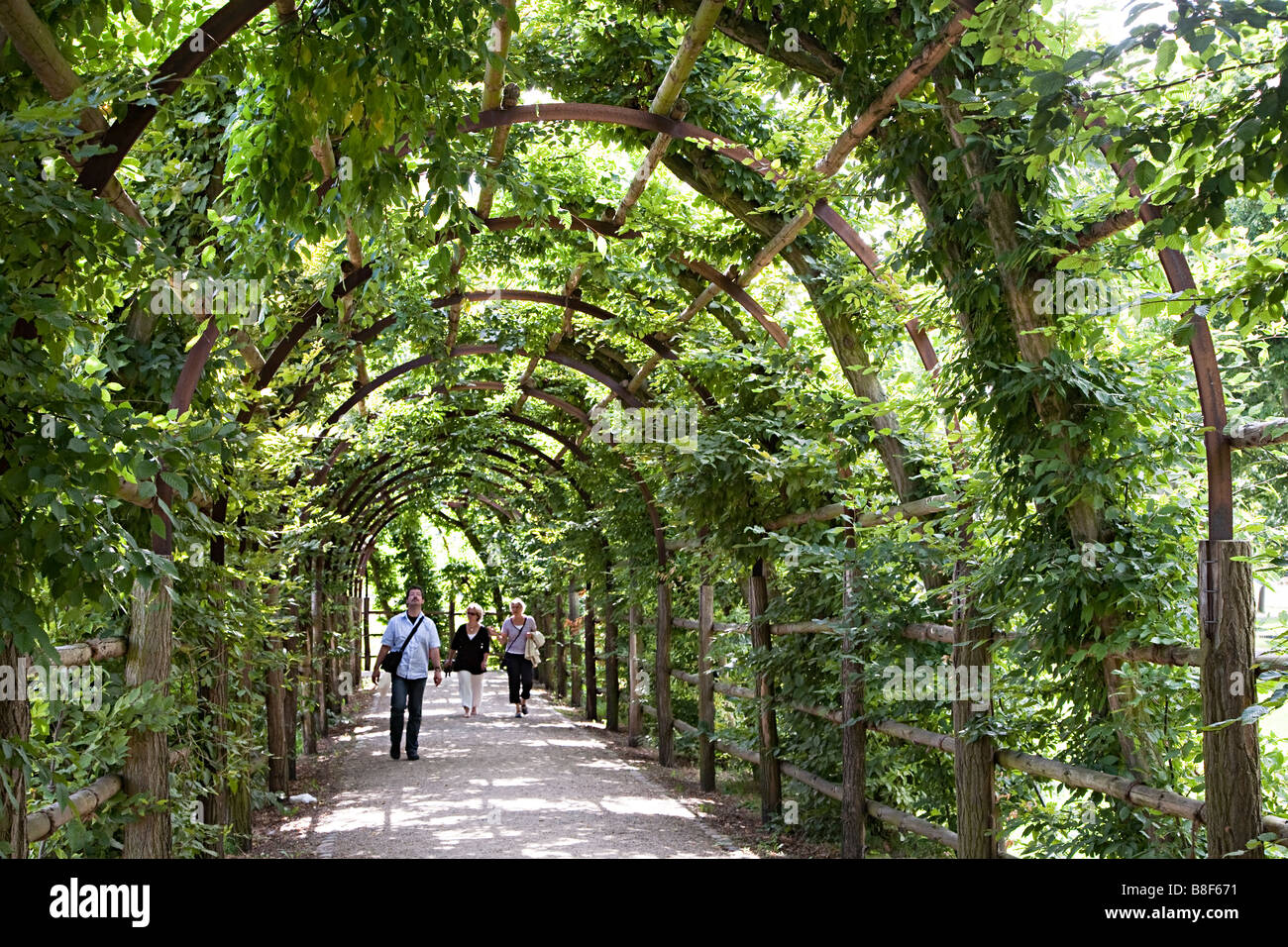 People walking through shade of pathway with plants trained over arches Schwerin Germany - Stock Image