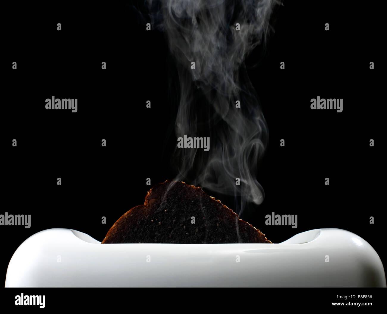 Smoking Burnt Toast in Toaster - Stock Image