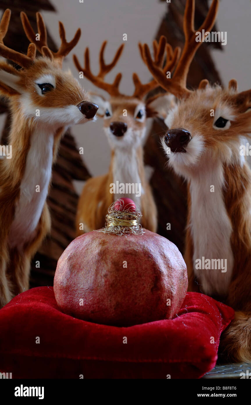 Deer (stuffed animal) standing around a red pillow with a pomegranate - Stock Image
