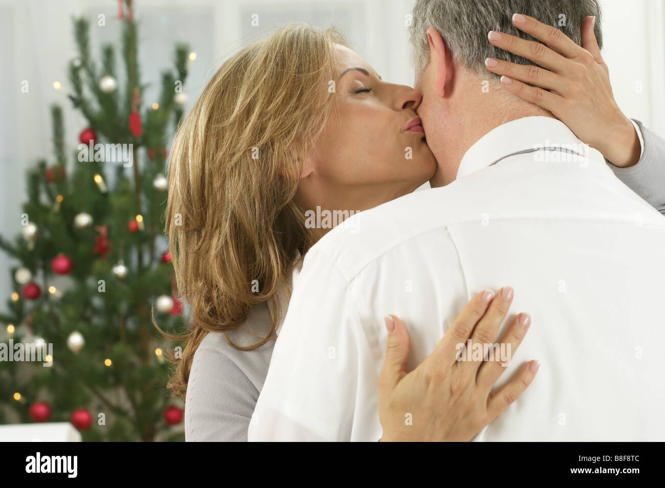 Kissing couple in front of a Christmas tree - Stock Image