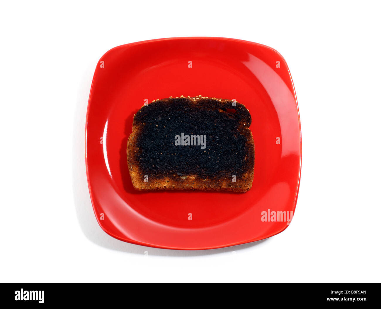 Burnt Toast on Red Plate - Stock Image