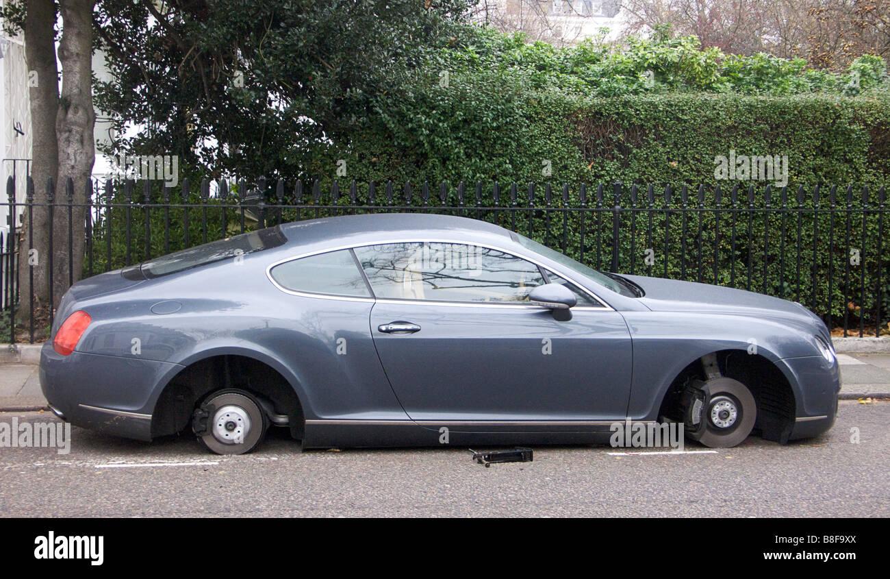 Luxury Bentley minus its wheels. Stolen wheels. - Stock Image