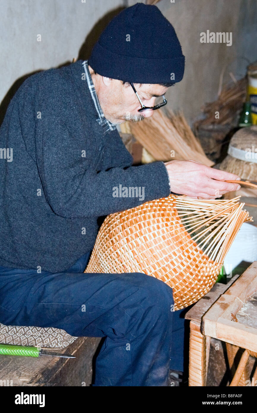 Basket weaver at work in a factory shop in Camacha Madeira - Stock Image