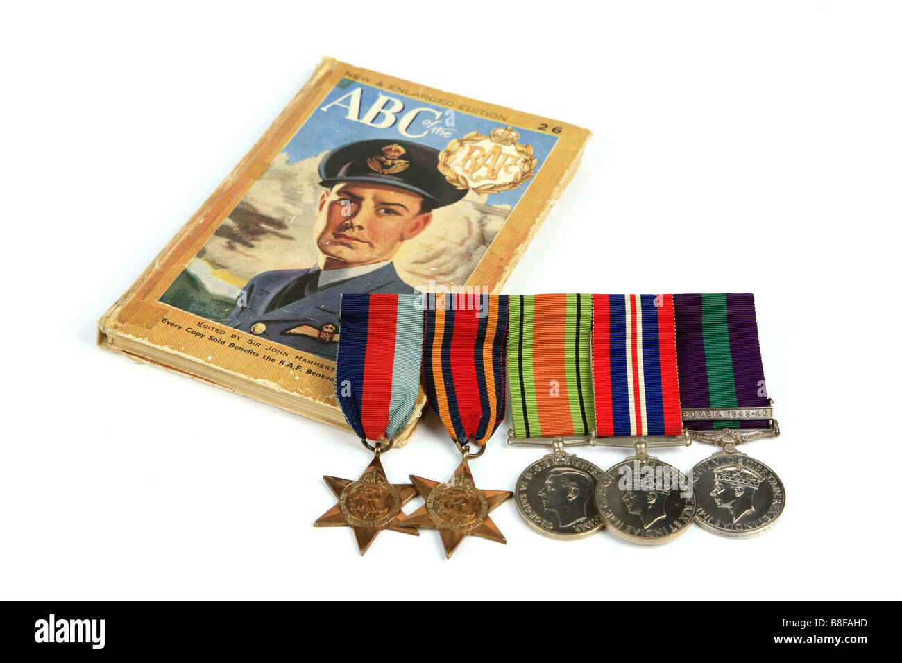 A WW2 Recruitment book and a group of British WW2 Medals against a white background - Stock Image