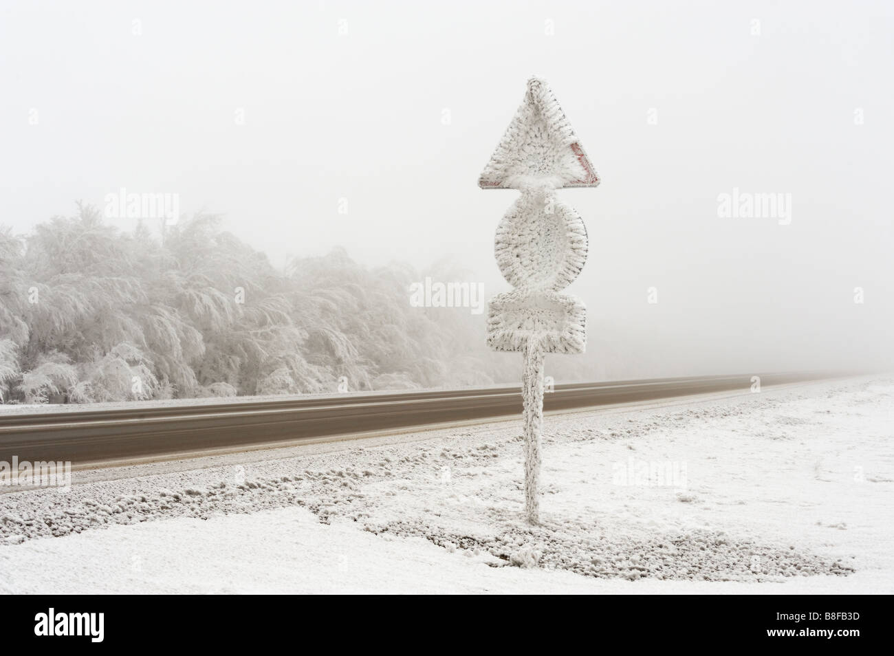 Winter road with hoar-frosted road signs. - Stock Image