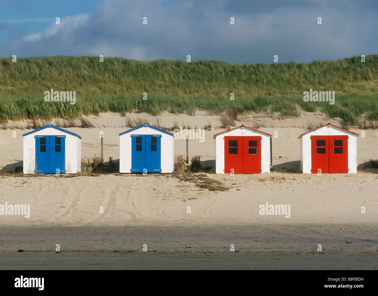 Blue and red boat houses at beach, Texel island, North Holland, Netherlands - Stock Image