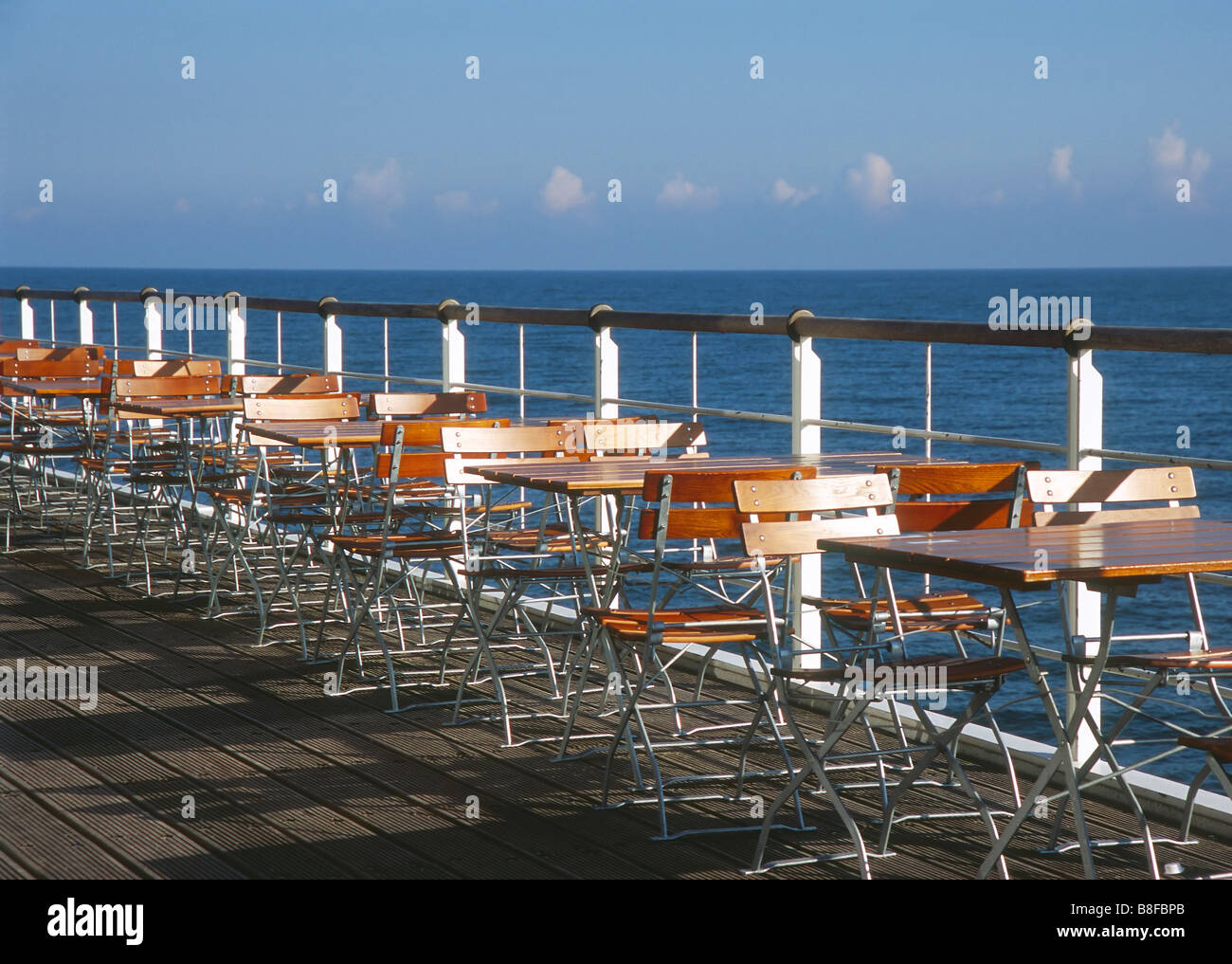 Empty chairs and tables on terrace at sea - Stock Image