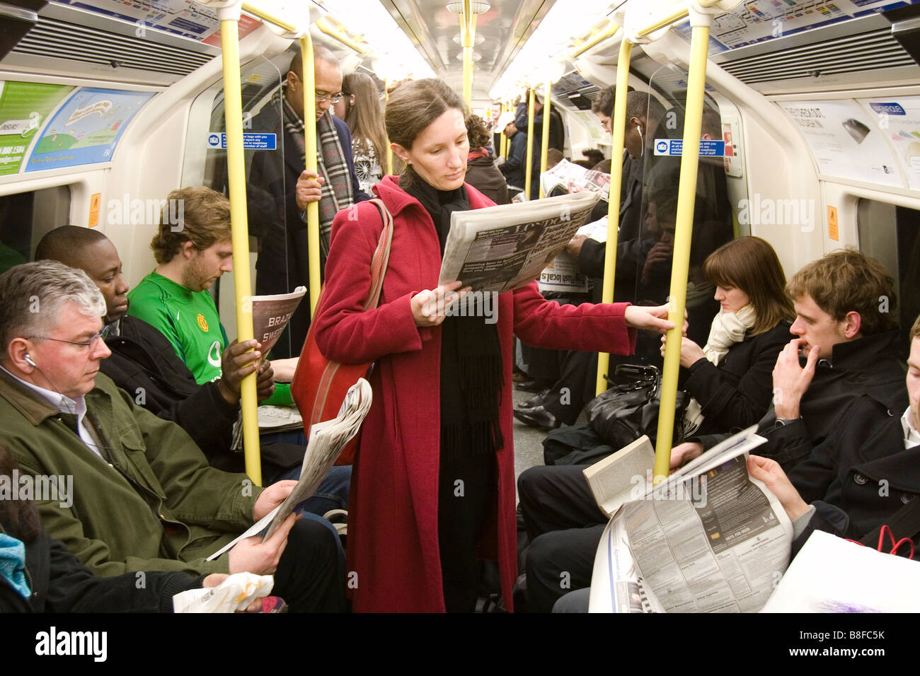 people reading newspapers on the london underground stock photo