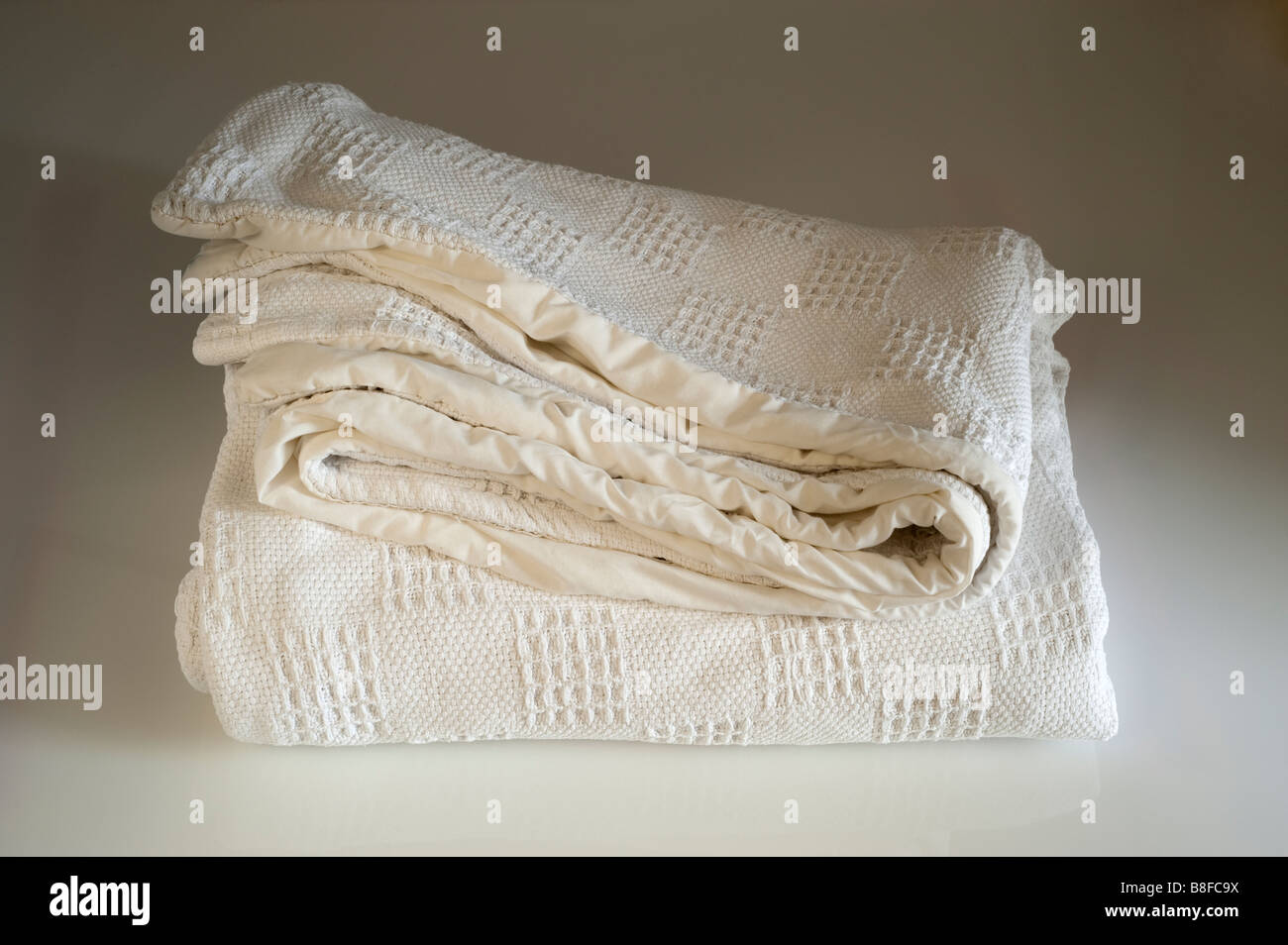 Thick white lined folded  blanket - Stock Image