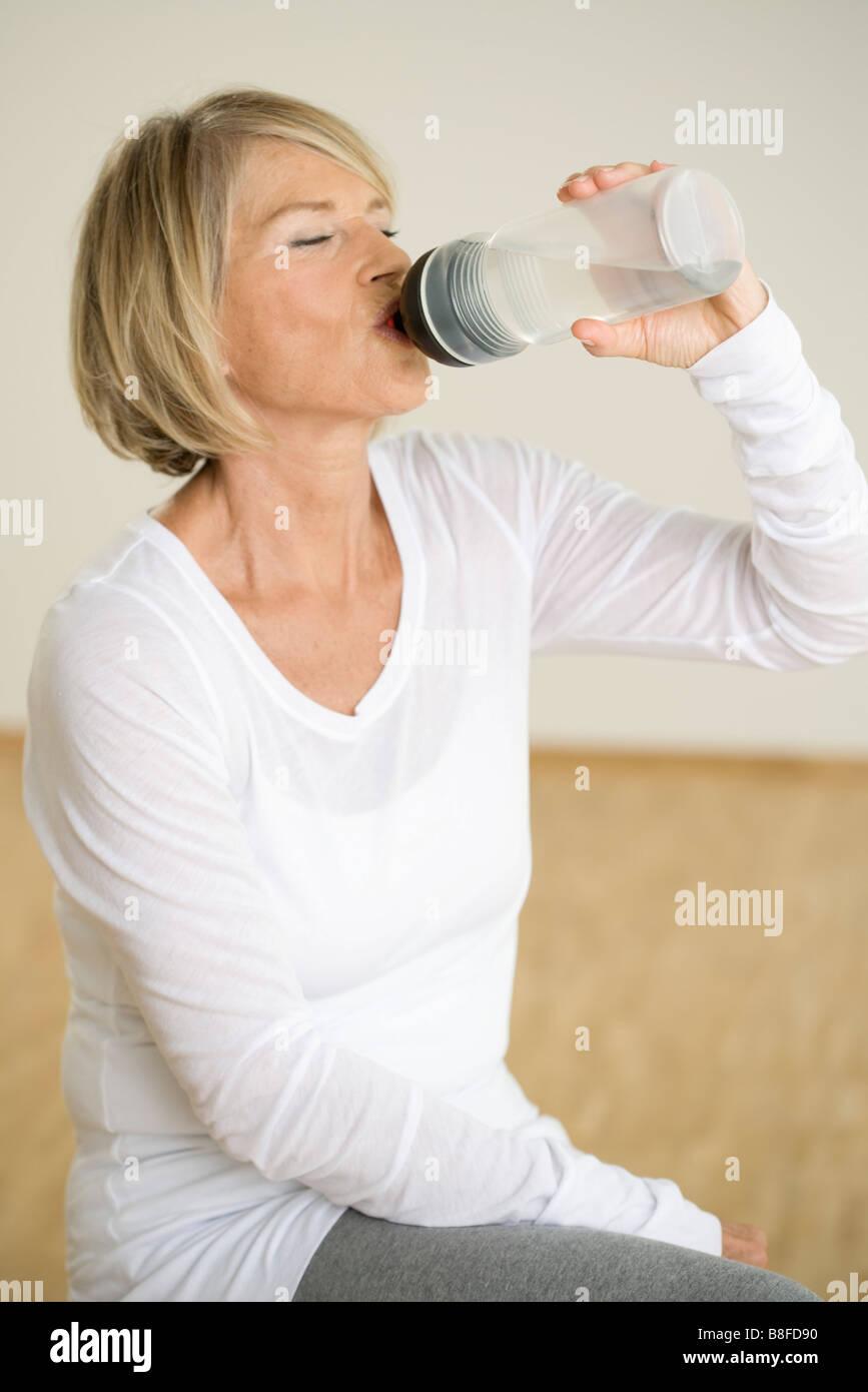Senior woman drinking water, Munich, Bavaria, Germany - Stock Image