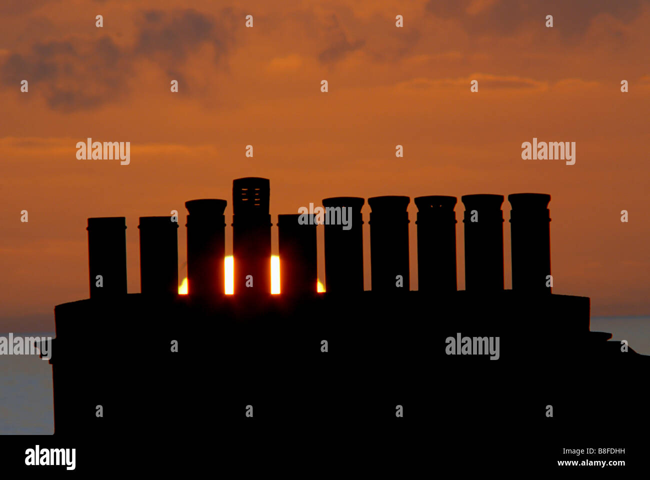 chimney stack with multiple chimney pots. sunset beyond - Stock Image