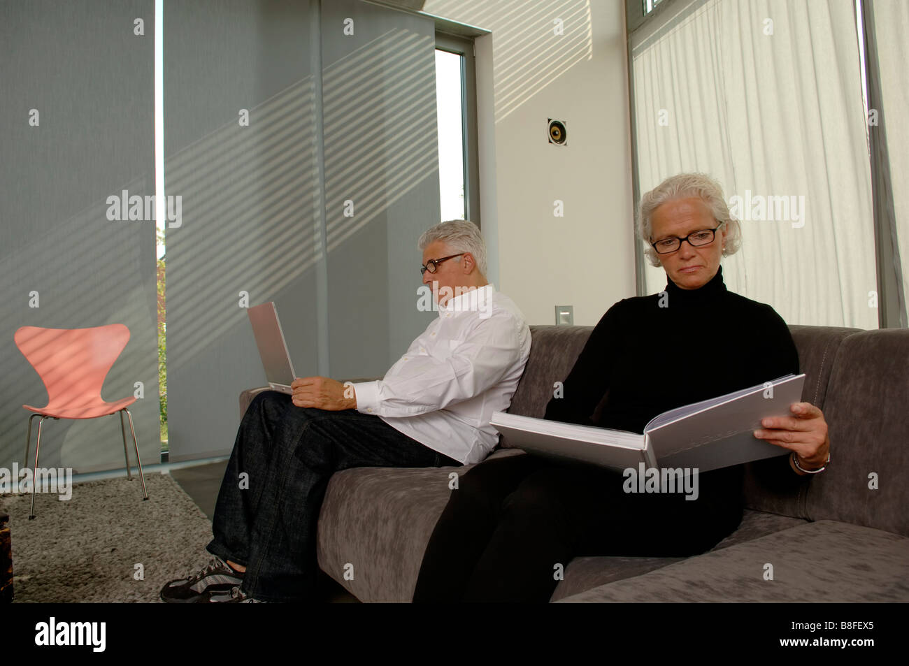 Senior man with a laptop next to a senior woman with a book, both sitting on a settee - Stock Image