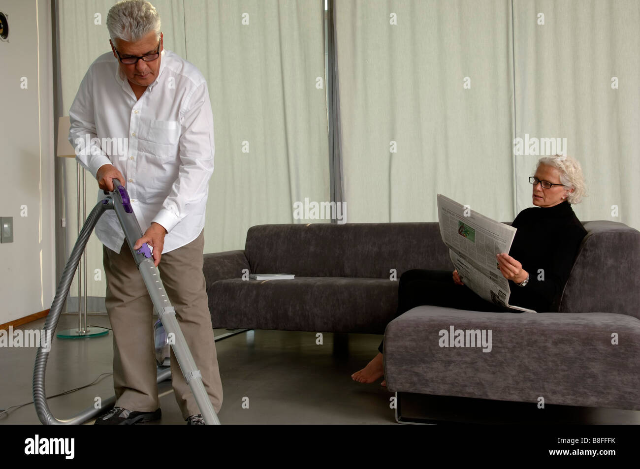 Senior man is vacuum-cleaning while his wife is reading newspaper - Stock Image
