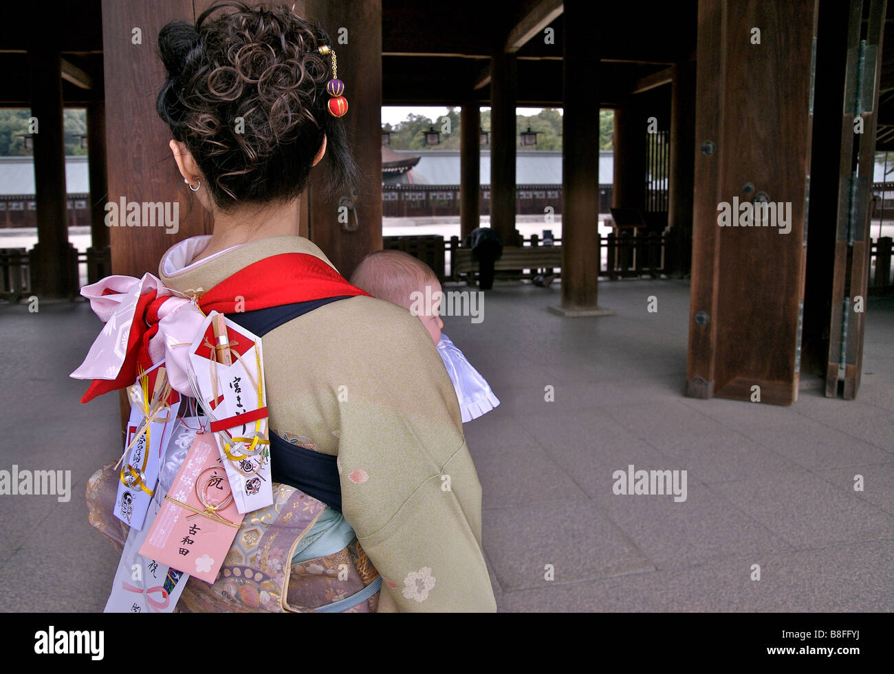 Japanese mother with baby at a Kashihara Shrine for a blessing ceremony. Note the items pinned to the back of her - Stock Image