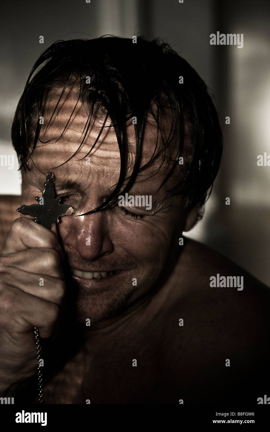 An extremely distressed and emotional man is sobbing as he holds his crucifix close to his face in hope. - Stock Image