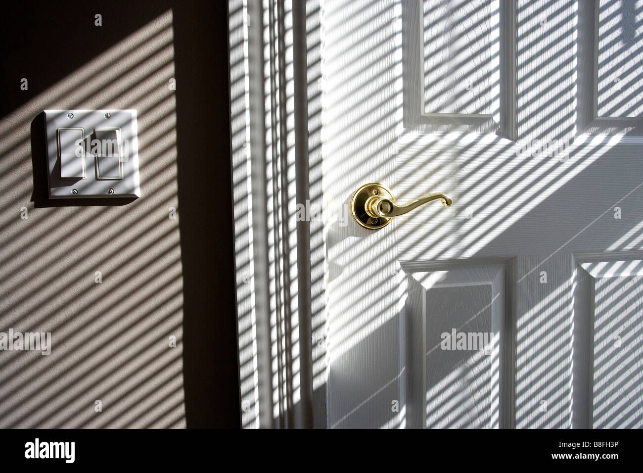 shadows on a wall from venetian blind - Stock Image