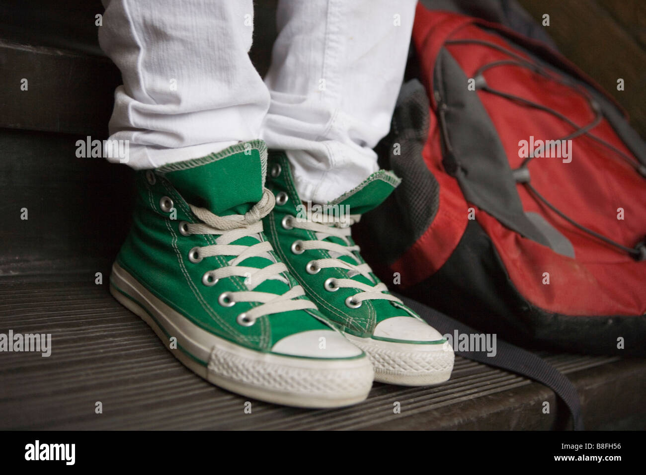 close up of green high top sneakers worn by teenager - Stock Image