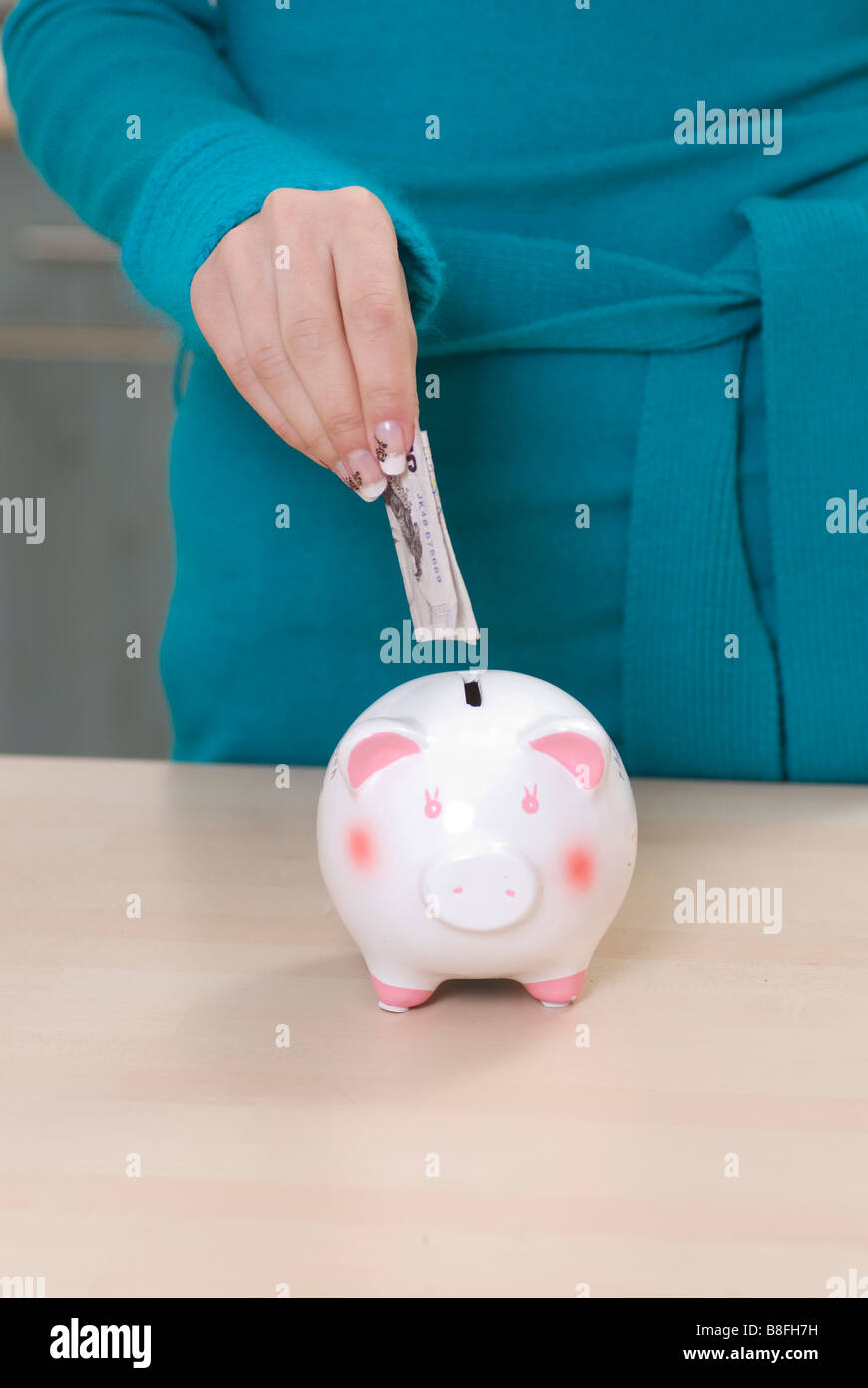 Close up of a woman saving money in a piggy bank - Stock Image