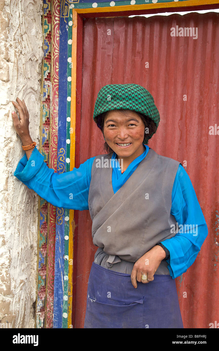 Tibetan woman in local style of dress against a red door. Tibet - Stock Image