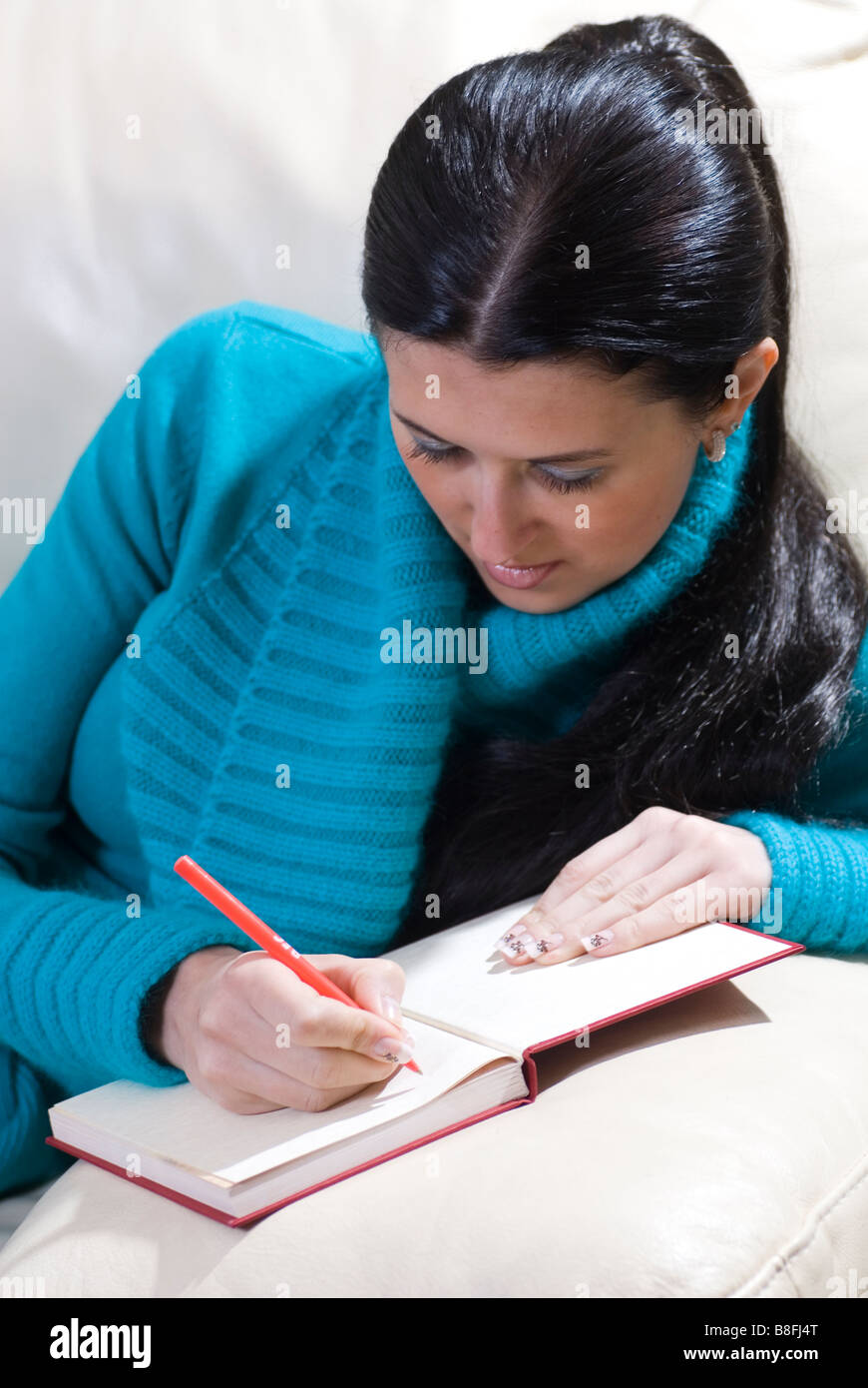 Beautiful young woman with long hair writing on her diary at home - Stock Image