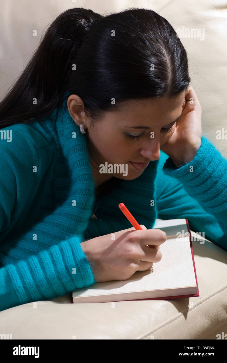 Young woman lying on sofa and writing her diary - Stock Image