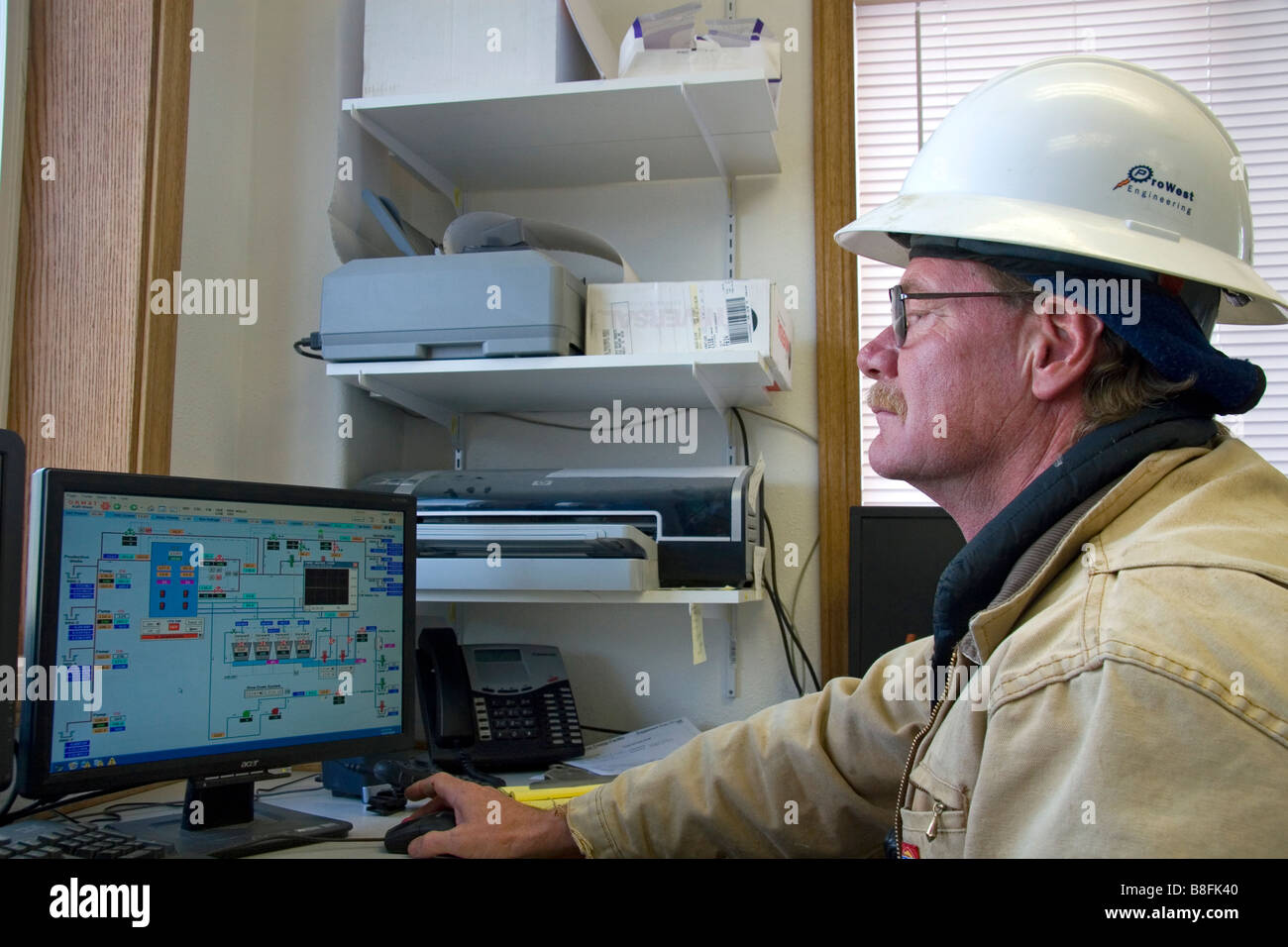 Operator using computers to monitor the system of a geothermal power plant in Malta Idaho USA - Stock Image