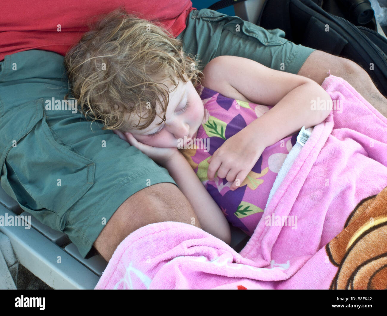 pink cheeked, long lashed, tousled red haired girl child sleeps in her father's lap on the beach at Sayulita, - Stock Image