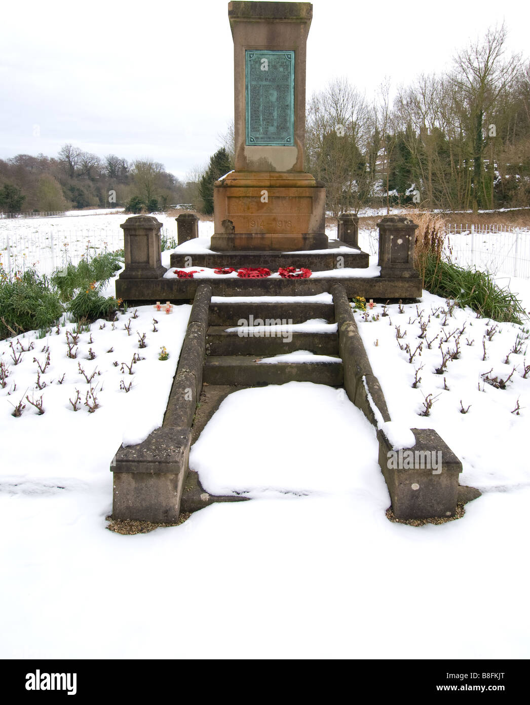 Poppy wreaths laid at a war memorial with a resent snow fall. - Stock Image