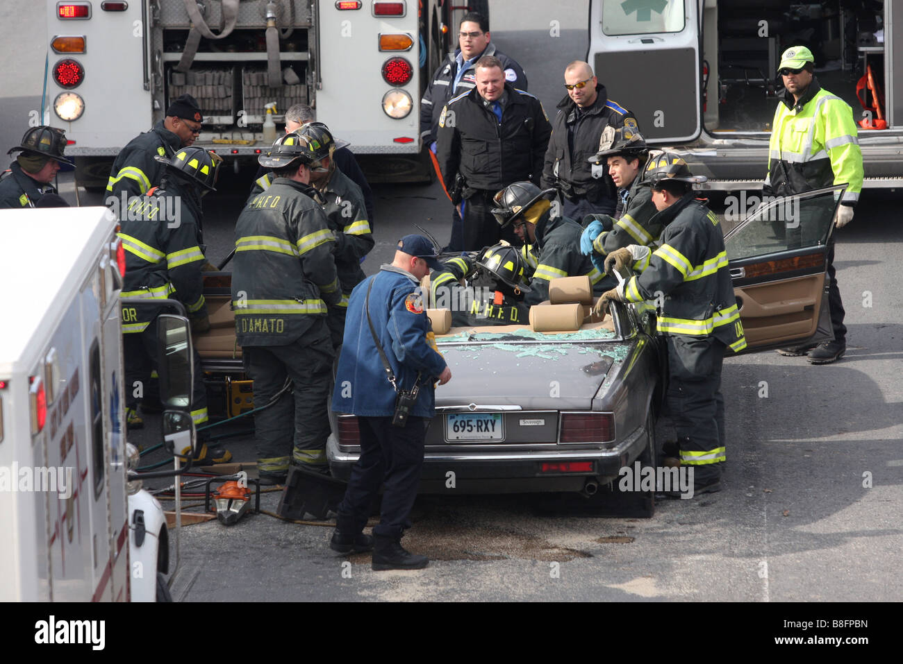 Firefighters extricate a woman from a Jaguar auto after cutting the roof off following a crash with a tractor trailer. - Stock Image