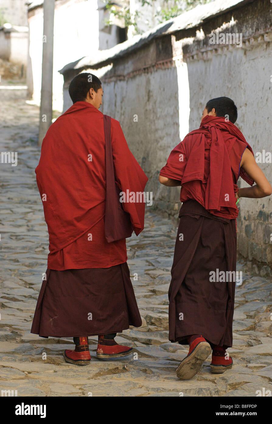 Tibetan monks walking along the narrow streets of  Tashilunpo monastery, Shigatse,Tibet - Stock Image