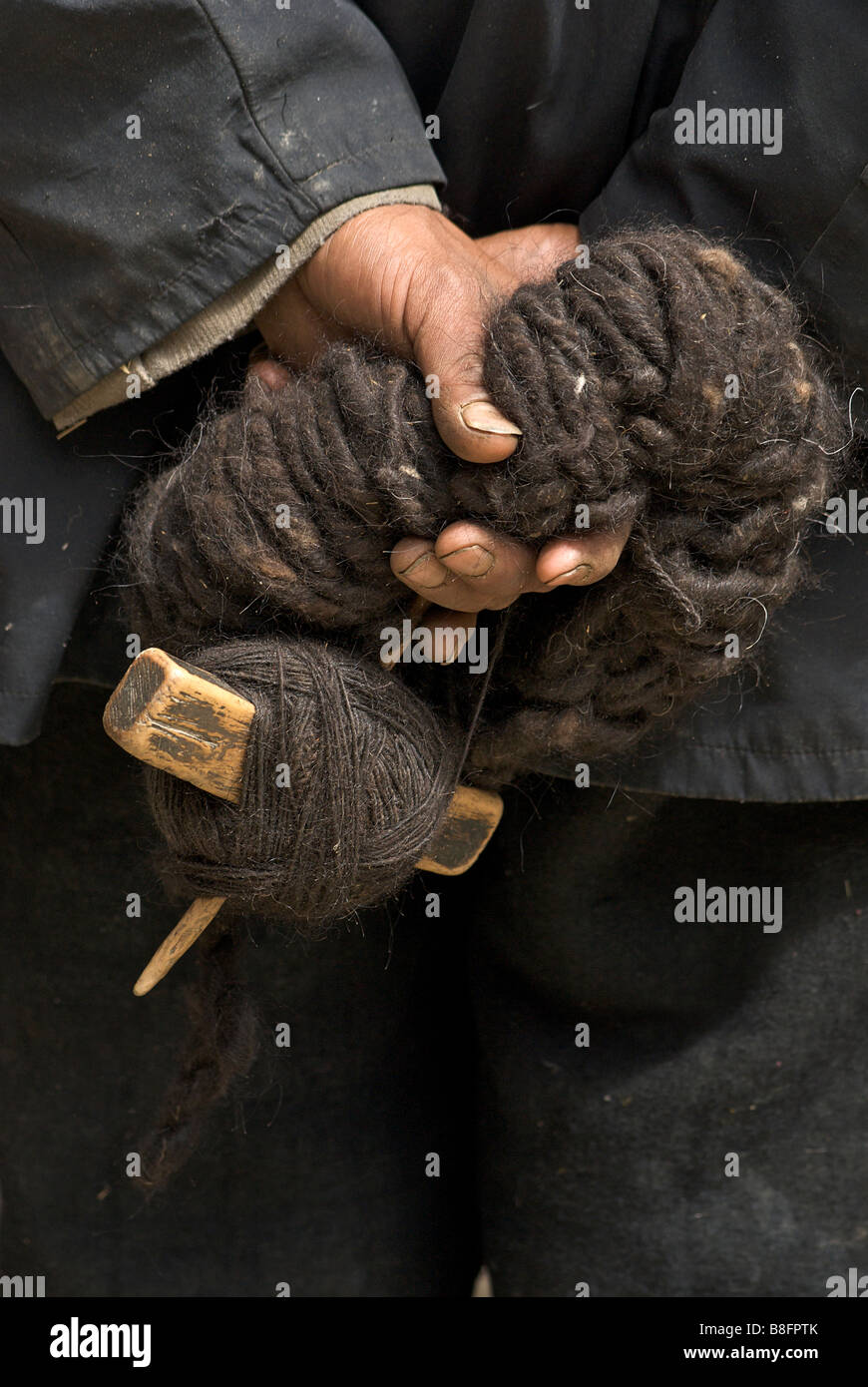 Tibetan man's hands - holding raw wool and spinning device. Sakya, Tibet Stock Photo