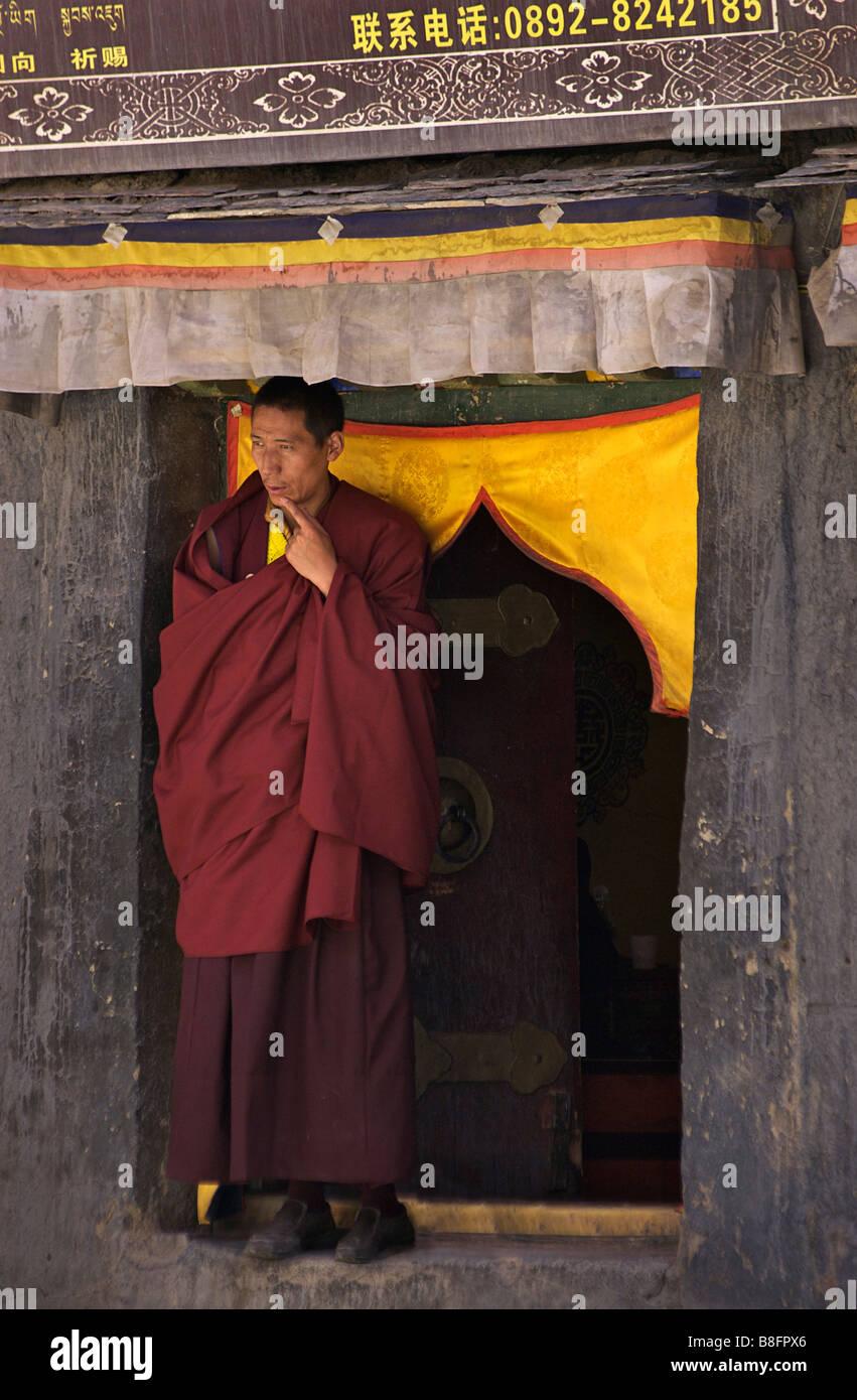 Tibetan buddhist monk standing in a doorway, Sakya, Tibet - Stock Image