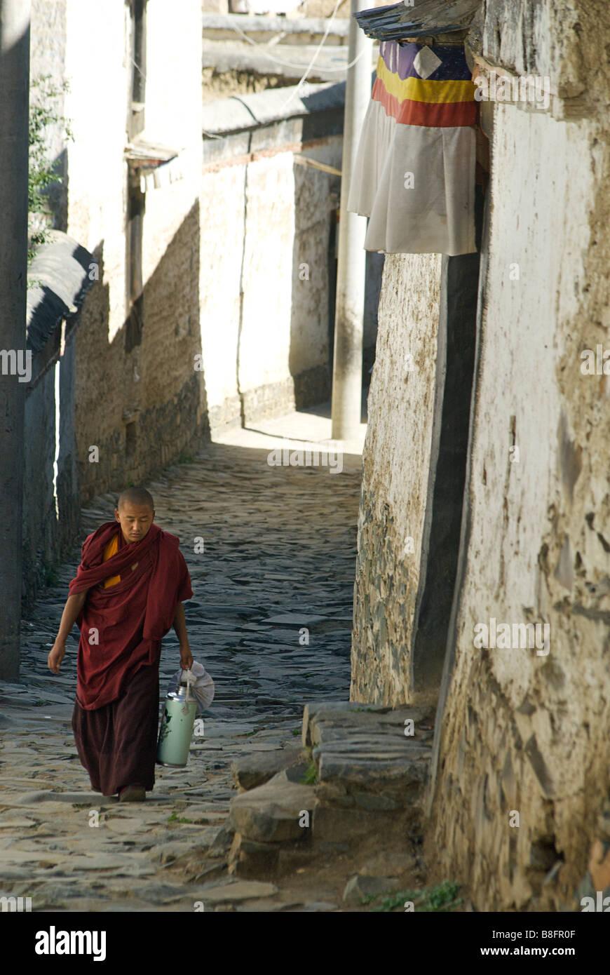 Tibetan monk walking along the narrow streets of  Tashilunpo monastery, Shigatse,Tibet - Stock Image