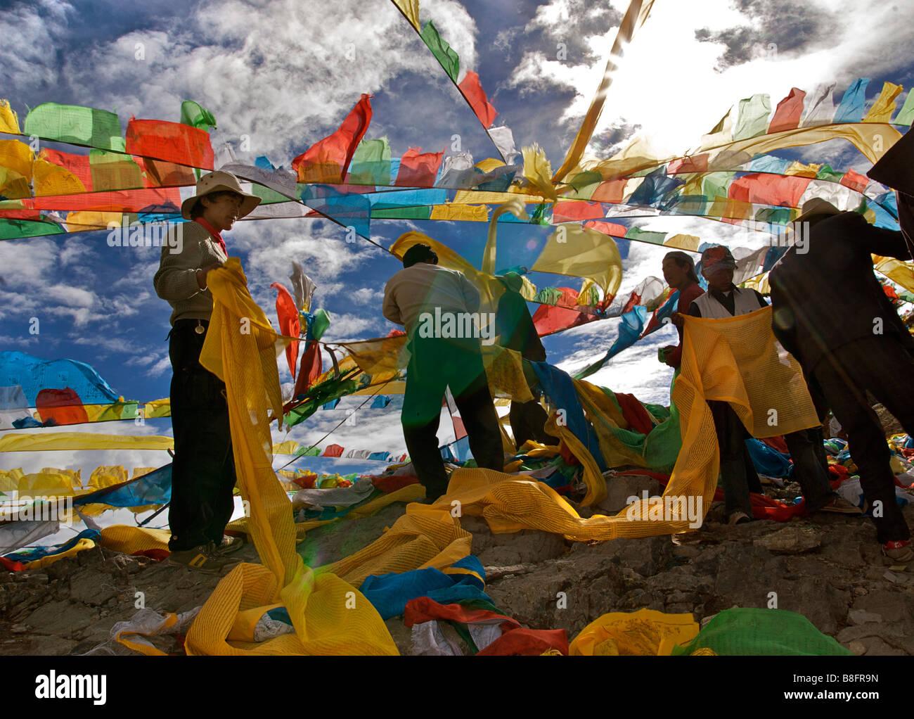 Tibetan men collecting loose prayerflags, Nam Tso Lake, Tibet - Stock Image