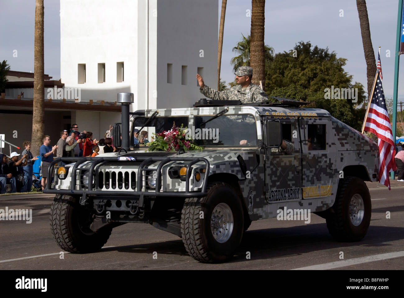 US Army in the Fiesta Bowl Parade with a camouflaged hummer.  A U.S. flag is off the backside and a soldier is waving Stock Photo