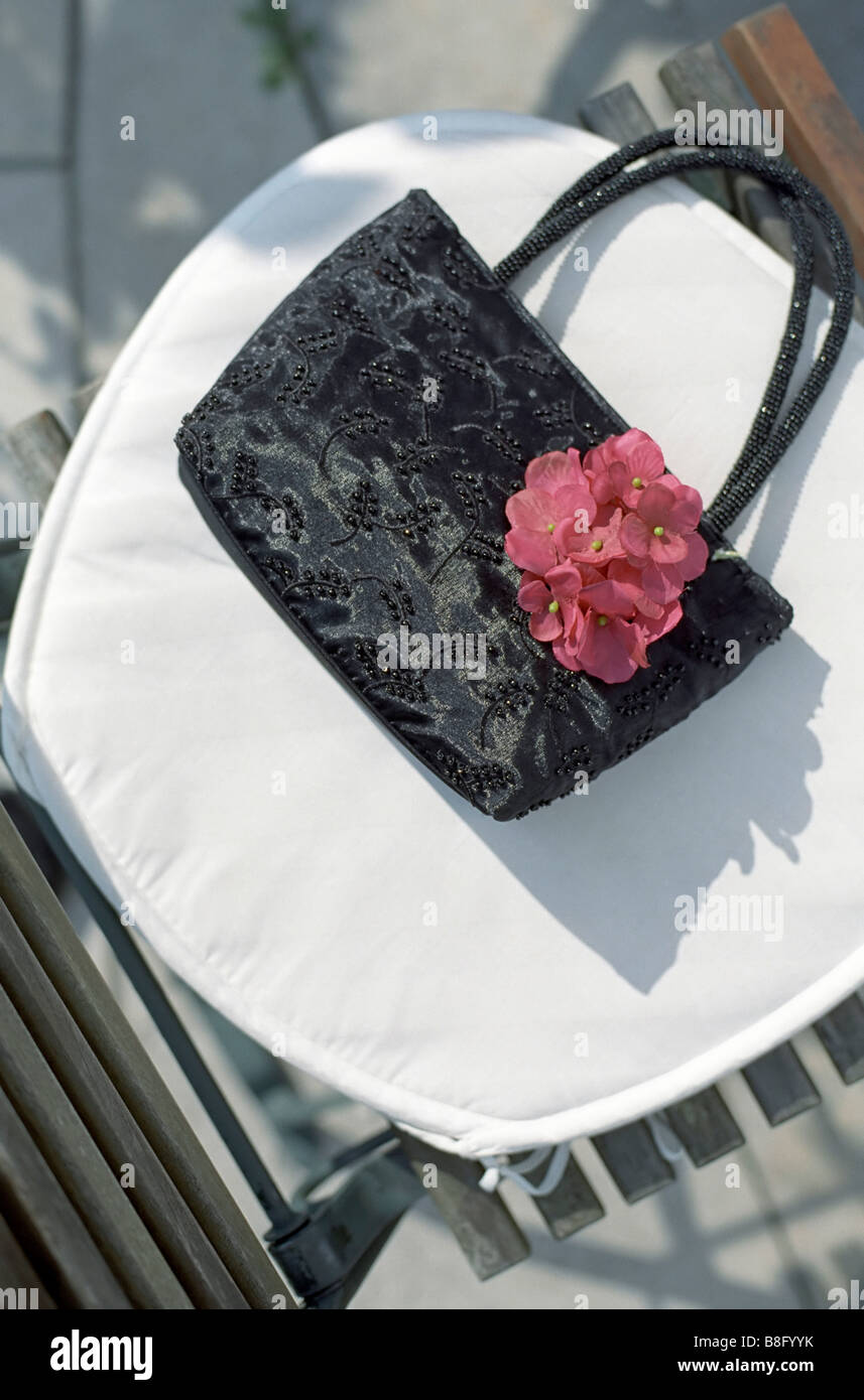 Handbag made of shiny Cloth on a Lawn Chair - Accessory - Textiles - Stock Image
