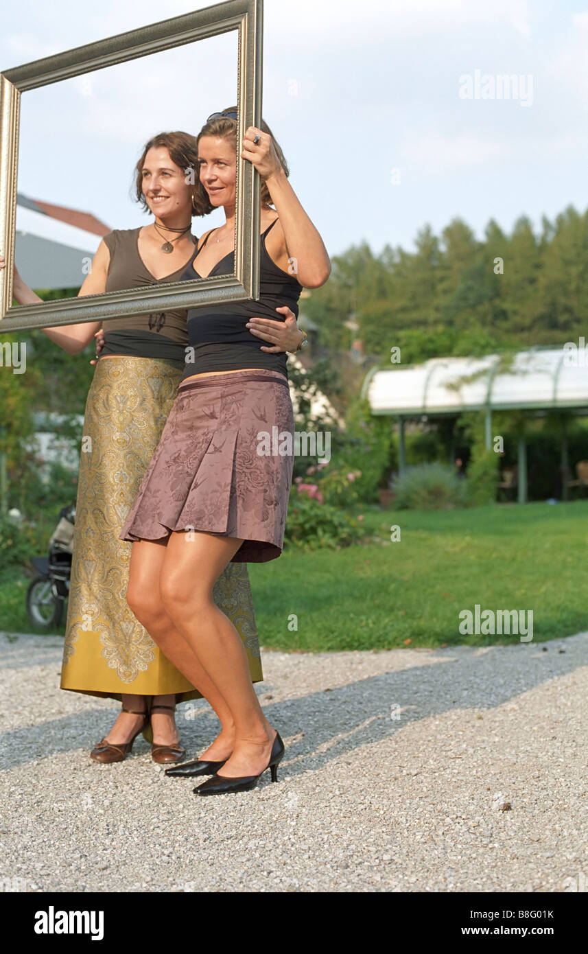 Someone taking Pictures of two young Women trough a Frame - Family Party - Garden - Stock Image